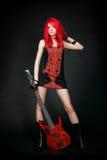Muchacha del eje de balancín del Redhead con la guitarra baja roja Imágenes de archivo libres de regalías