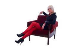 Muchacha del encanto de la manera que se sienta en silla suave. Imagen de archivo libre de regalías