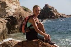 Muchacha del escalador que se sienta en un acantilado con el océano en el fondo Imágenes de archivo libres de regalías