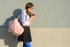 Muchacha del estudiante del adolescente con la mochila de la escuela y el vidrio de la bebida, en perfil, fondo una pared gris al Fotografía de archivo