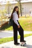 Muchacha del estudiante del adolescente con paseo marrón largo en el cierre u del pennyboard fotos de archivo