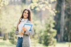 Muchacha del estudiante afuera con los auriculares que caminan con los cuadernos en parque Fotografía de archivo libre de regalías