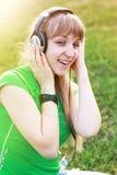 Muchacha del estudiante afuera en el parque que escucha Imagen de archivo libre de regalías