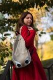 Muchacha del estudiante afuera en la sonrisa del parque del otoño feliz Foto de archivo libre de regalías