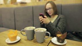 Muchacha del estudiante al usar sorprendido vidrios por el mensaje de texto de su novio Ella usando el app en smartphone en café almacen de metraje de vídeo