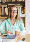 Muchacha del estudiante con café de consumición del libro en biblioteca Imagen de archivo libre de regalías