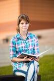 Muchacha del estudiante con el cuaderno en banco Parque del campus del verano Imagenes de archivo