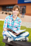 Muchacha del estudiante con el cuaderno en banco Parque del campus del verano Imágenes de archivo libres de regalías