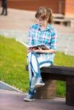 Muchacha del estudiante con el cuaderno en banco Parque del campus del verano Fotografía de archivo libre de regalías