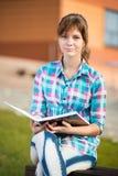 Muchacha del estudiante con el cuaderno en banco Parque del campus del verano Imagen de archivo libre de regalías