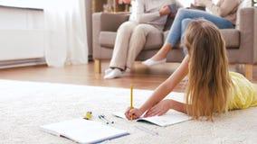 Muchacha del estudiante con el cuaderno que miente en piso en casa almacen de video