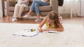 Muchacha del estudiante con el cuaderno que miente en piso en casa almacen de metraje de vídeo