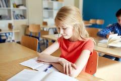Muchacha del estudiante con el libro en la lección de la escuela Imágenes de archivo libres de regalías