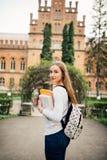 Muchacha del estudiante con el libro en outfoors de la universidad Fotografía de archivo