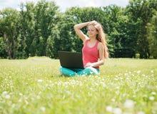 Muchacha del estudiante con el ordenador portátil al aire libre Mujer joven de la universidad o del estudiante universitario en l Fotos de archivo libres de regalías