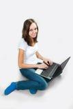 Muchacha del estudiante con el ordenador portátil en fondo gris Fotografía de archivo