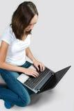 Muchacha del estudiante con el ordenador portátil en fondo gris Fotografía de archivo libre de regalías