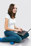 Muchacha del estudiante con el ordenador portátil en fondo gris Imagen de archivo