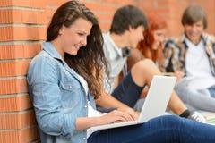Muchacha del estudiante con el ordenador portátil y los amigos afuera Imagen de archivo libre de regalías