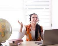 Muchacha del estudiante con el ordenador portátil y los heaphones Fotos de archivo libres de regalías
