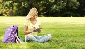 Muchacha del estudiante con el panel táctil y mochila en parque Fotos de archivo