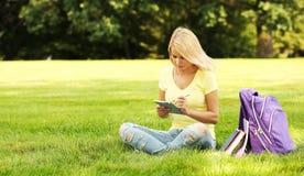 Muchacha del estudiante con el panel táctil y mochila en parque Imágenes de archivo libres de regalías