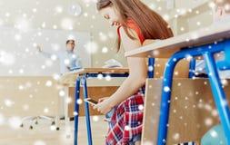 Muchacha del estudiante con el smartphone que manda un SMS en la escuela Fotos de archivo libres de regalías