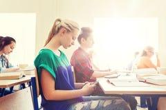 Muchacha del estudiante con el smartphone que manda un SMS en la escuela Imagenes de archivo