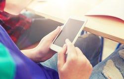 Muchacha del estudiante con el smartphone que manda un SMS en la escuela Fotografía de archivo libre de regalías