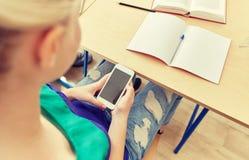 Muchacha del estudiante con el smartphone que manda un SMS en la escuela Imágenes de archivo libres de regalías
