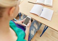 Muchacha del estudiante con el smartphone que manda un SMS en la escuela Fotos de archivo
