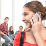 Muchacha del estudiante con el teléfono celular en la escuela Foto de archivo libre de regalías