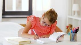 Muchacha del estudiante con la escritura del libro al cuaderno en casa almacen de video