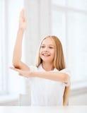 Muchacha del estudiante con la mano para arriba en la escuela Imágenes de archivo libres de regalías