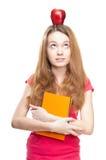 Muchacha del estudiante con la manzana en su cabeza Fotos de archivo libres de regalías