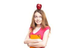 Muchacha del estudiante con la manzana en su cabeza Imagen de archivo