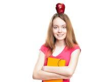 Muchacha del estudiante con la manzana en su cabeza Imagen de archivo libre de regalías