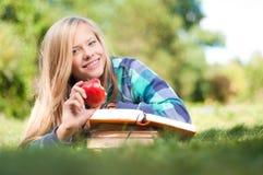 Muchacha del estudiante con la manzana y los libros Imágenes de archivo libres de regalías