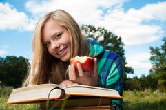 Muchacha del estudiante con la manzana y los libros Imagen de archivo