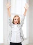 Muchacha del estudiante con las manos para arriba en la escuela Imágenes de archivo libres de regalías