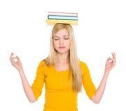 Muchacha del estudiante con los libros en meditating principal Foto de archivo libre de regalías
