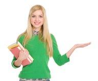 Muchacha del estudiante con los libros que muestran algo en la palma Imágenes de archivo libres de regalías