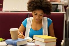 Muchacha del estudiante con los libros y el café en conferencia Fotos de archivo