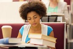 Muchacha del estudiante con los libros y el café en conferencia Imagen de archivo