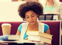 Muchacha del estudiante con los libros y el caf? en conferencia foto de archivo