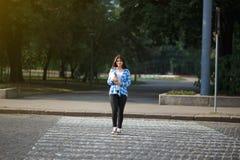 Muchacha del estudiante con los libros y la mochila que cruzan la calle Manera a Imagen de archivo libre de regalías