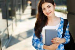 Muchacha del estudiante con los libros y la mochila que se colocan cerca de fachada moderna Fotografía de archivo libre de regalías