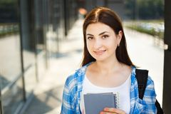 Muchacha del estudiante con los libros y la mochila que se colocan cerca de fachada moderna Fotos de archivo libres de regalías