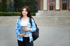 Muchacha del estudiante con los libros y la mochila que se colocan en fondo de la ciudad Imagen de archivo libre de regalías