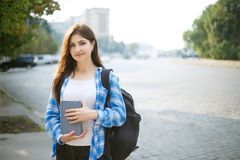 Muchacha del estudiante con los libros y la mochila que se colocan en sol en el CIT Imagen de archivo
